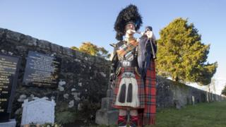 Lone piper at graveside