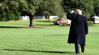 US President Donald Trump raises his fist as he walks on the South Lawn before boarding Marine One at the White House, 13 October 2018