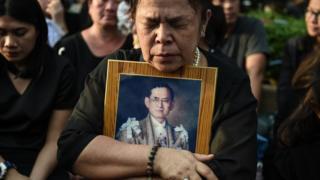 Una señora tailandesa se aferra a una fotografía del fallecido rey