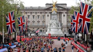 Runners heading down The Mall during the 2019 London Marathon with Buckingham Palace in the background