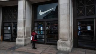 A woman reads the sign on the door of the closed Niketown store on Oxford Street, London.
