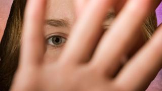 Mulher com a mão em frente ao rosto