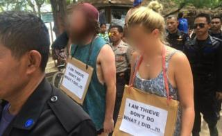 "Western man and woman being paraded by Indonesian police and security guards with a sign around their necks reading ""I am thieve [sic] don't do what I did...!!!"""