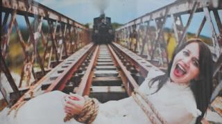 An poster shows a posed shot of a woman screaming at the camera while lying on a railway bridge, bound with rope, while a train approaches