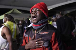 A man, among a first group of Nigerians repatriated from South Africa following xenophobic violence, recites the national anthem after arriving in Lagos, on September 11, 2019.