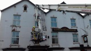 Fire officer on a crane in front of the Londesborough pub