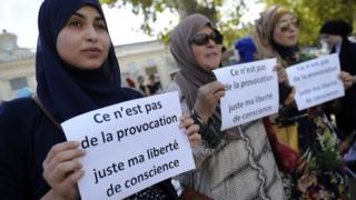 "Women hold signs reading ""Is it not a provocation, just my freedom of conscience"" during a ""headscarf march"" in Avignon"