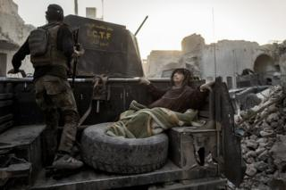 An elderly woman is driven through Mosul, Iraq, as the Golden Division help her flee the front line in extreme heat.