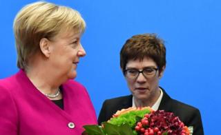 German Chancellor and leader of the Christian Democratic Union (CDU) Angela Merkel (L) receives flowers next to CDU's Secretary General Annegret Kramp-Karrenbauer before a CDU leadership meeting at the party's headquarters on October 29, 2018 in Berlin