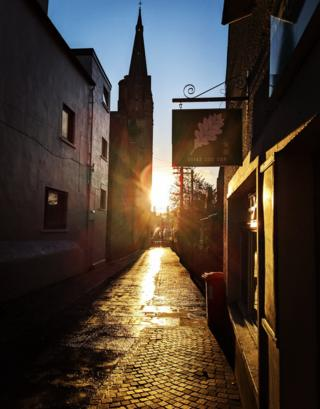 A sunset in Inverness looking down a street, with a wheelie bin in the right hand side