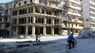Житель Алеппо на велосипеде едет по разрушенной улице
