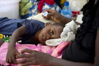 """In this picture, a boy suffering from cholera receives treatment at a cholera centre in Anse D""""Hainault, Haiti, on 11 October, 2016. The UN says Hurricane Matthew has increased the risk of a """"renewed spike"""" in the cholera cases."""