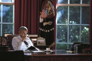 Obama sits at his desk