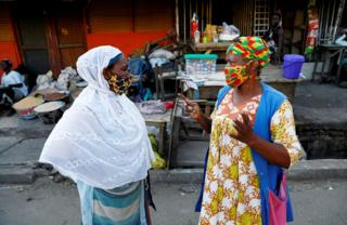 Two African women in colourful face masks speaking to each other on the street.