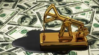 Maquinaria para extraer petróleo de juguete sobre un fondo de dólares