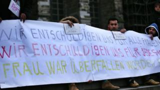 Migrants from Egypt and Morocco held up a banner at Cologne station apologising to women for the violence (12 Jan)