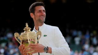 Serbia's Novak Djokovic with the trophy as he celebrates winning the final against Switzerland's Roger Federer