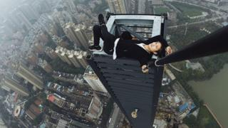 Wu Yongning uses a selfie stick to photograph himself reclining on top of a structure far above the surrounding buildings