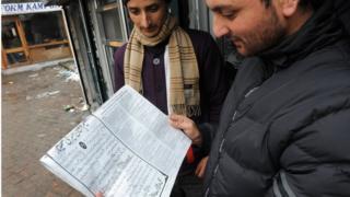 Men reading a newspaper in Srinagar