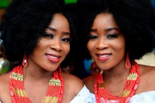 Identical twin sisters wearing matching jewellery and hairstyles smile for the camera.