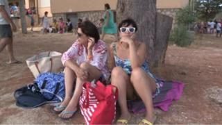 A still from EVN footage shows two women in holiday clothes sitting on the floor in Calampiso, which was evacuated on 12 July 2017