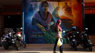 A woman walks past a mural at the central Siti Khadijah market
