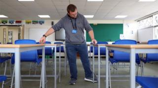 science A school caretaker ensures desks are properly spaced