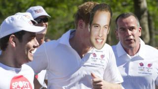 Prince Harry wears a Prince William mask.