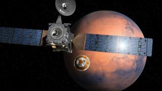 Bajo la nave nodriza TGO el módulo de investigación. En el fondo Marte.