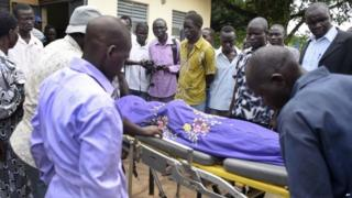 Relatives and other mourners watch as the body of South Sudanese journalist Peter Julius Moi is taken into the mortuary in Juba, South Sudan Thursday, 20 August 2015