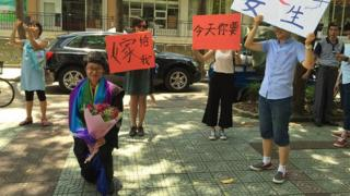 "Jean Ouyang proposes to her girlfriend as the people in the background wave banners saying ""Will you marry me today?"""