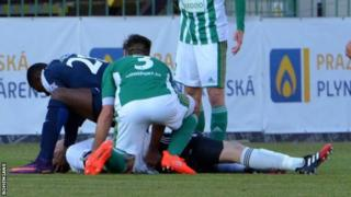 Francis Koné and other players dey try to help player wey dey ground