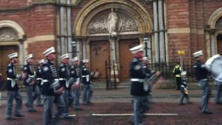 The parade observed a single drumbeat passing by St Patrick's Catholic Church in Belfast