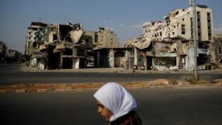 امرأة تسير أمام مبان مدمرة في حمص (أرشيف)