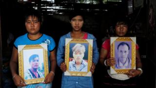Villagers hold up pictures of the murdered men