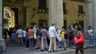 Cubans stand in line to pay tribute and to write in the condolence book for Eusebio Leal
