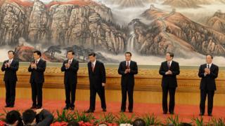 Seven men in dark suits take to the stage at the CCP Congress in Beijing - the new standing committee of the Party's politburo.