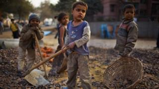 Indian children work nearby to their parents at a construction project in front of the Jawaharlal Nehru Stadium on 30 January 2010 in New Delhi, India