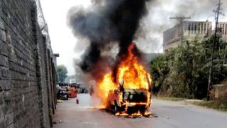 A burning vehicle in a street