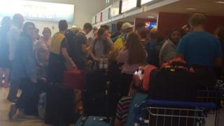 Passengers queue for information at Belfast International Airport