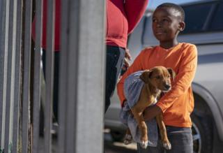 A South African boy waits with his dog to see a Veterinarian outside the Mdzananda Animal Clinic in Khayelitsha, Cape Town, South Africa