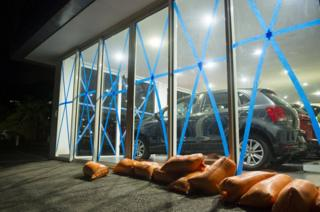 Car dealership windows are taped up.