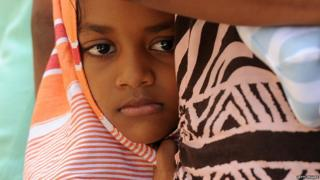 A child amongst a group of Sri Lankan asylum seekers sent back by Australia looks on before entering the magistrate's court in the southern port district of Galle on July 8, 2014