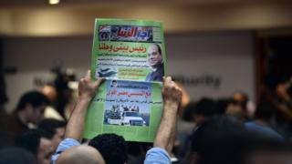 رجل يحمل جريدة مؤيدة للسيسي