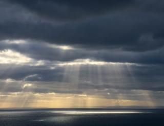 Sun rays showing through clouds over sea