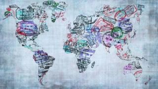 ప్రపంచ పటంపై వేరువేరు దేశాల స్టాంపు గుర్తులు వేసి ఉన్నాయి