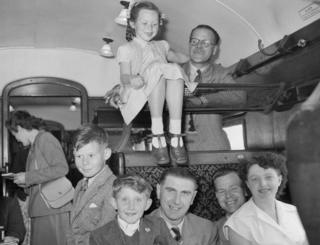Children and adults crammed together in carriage