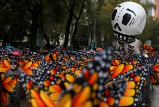 A balloon in the shape of a skeleton is pictured near participants dressed as Monarch butterflies during the annual Day of the Dead parade in Mexico City
