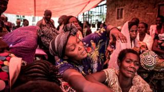 Women react when they see the coffin of someone killed by the Ugandan Allied Democratic Forces(ADF) rebel group in Beni, DR Congo