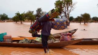 Un sinistré embarque ses effets dans une pirogue dans un quartier inondé de Niamey, le 5 septembre 2016.